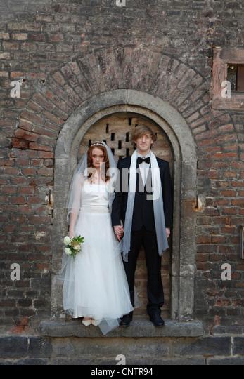 Frisch vermählte Paar stehen in Bogen Stockbild