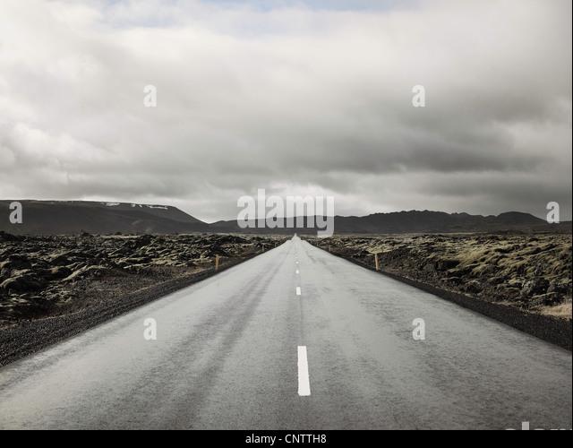 Landstraße unter bewölktem Himmel Stockbild