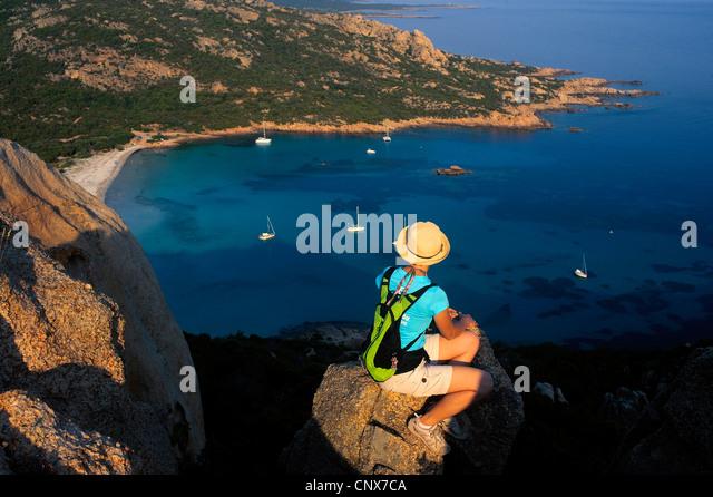 weibliche Wanderer sittin auf einem Felsen über der Bucht von Roccapina, Frankreich, Korsika Stockbild