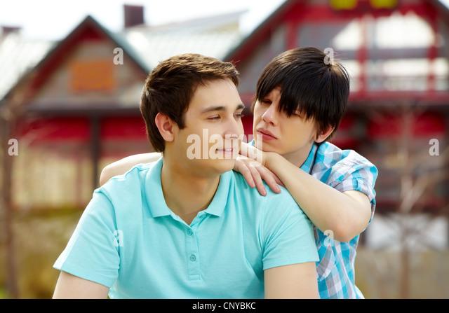 Gay Mann lächelnd, während sein Freund blickte ihn mit Stille Frage Stockbild
