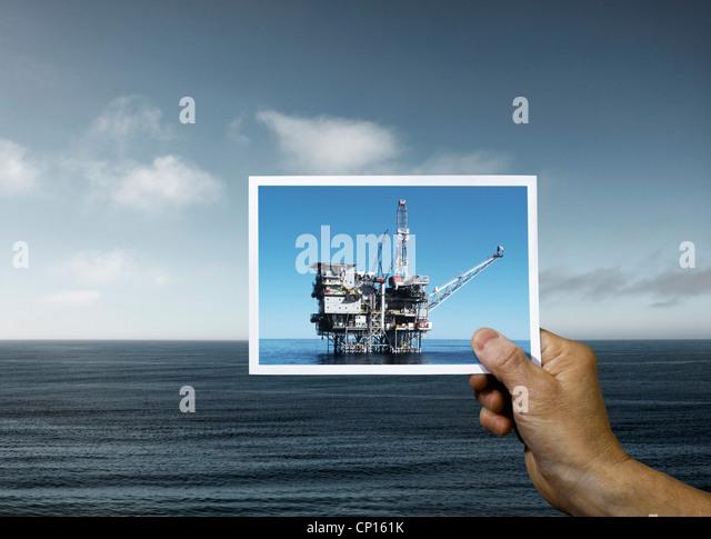 Hand mit Foto der Ölplattform Ozean Stockbild