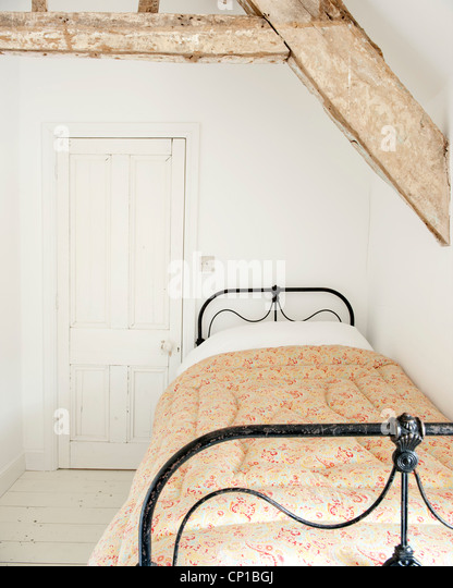 Einzelbett in Holzbalken Dachgeschoss Zimmer, Obstgarten Cottage, UK. Stockbild