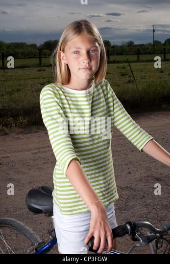 Elf Jahre altes Mädchen auf ihrem Fahrrad auf Feldweg. Stockbild