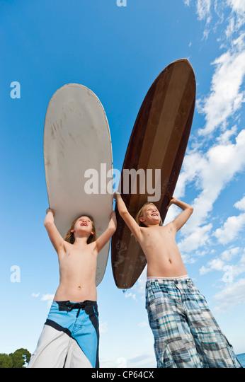 Spanien, Mallorca, Kinder mit Surfbrett am Strand Stockbild