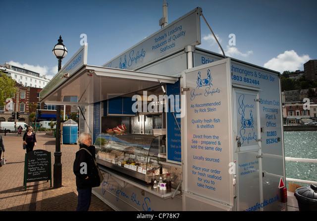 Hafen von Torquay, Devon, England, UK mittleren Alter Tourist am durchsuchen Seafoods Kai Fisch Stall Stockbild