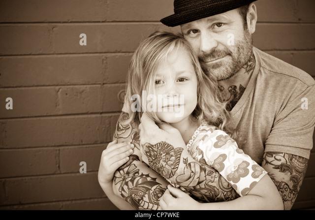 Vater hält seine fünfjährige Tochter und schaut in die Kamera. Stockbild