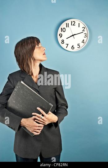 Geschäftsfrau betrachten eine Wanduhr, es ist bereits nach 08:00. Stockbild