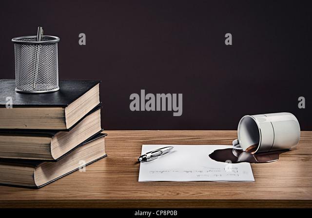 Kaffee verschüttet über Buchstaben auf Schreibtisch Stockbild