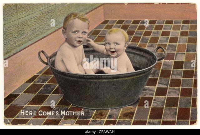 Frühe Postkarte von Babys Baden in einem Zinnbad, Vereinigtem Königreich, datiert 1913 Stockbild