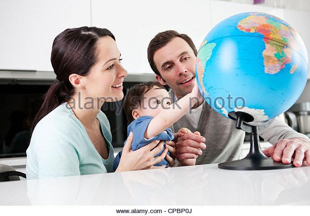 Ein paar und ihr Baby Sohn Blick auf einem Globus Stockbild
