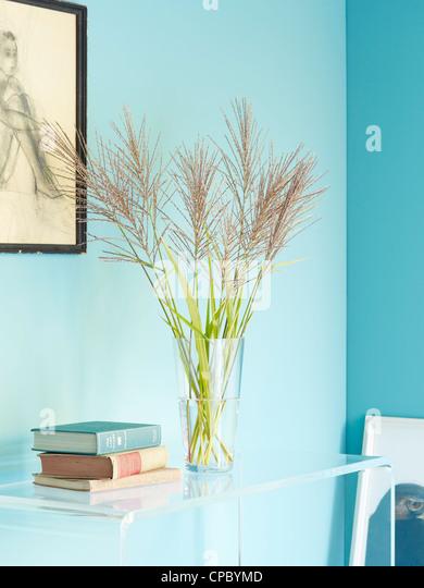 Vase mit Miscanthus auf Lucite Tisch. Stockbild