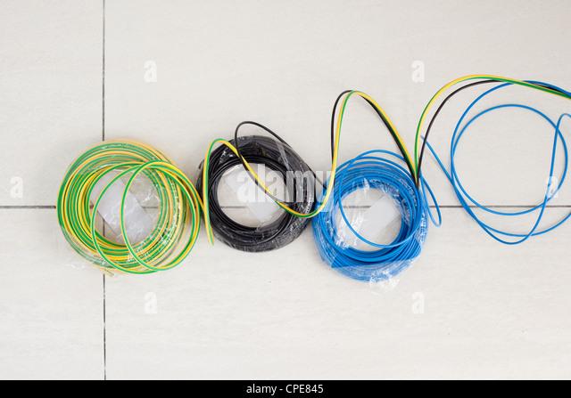 Elektrische Kabel Spule in drei Farben blau und grün gelb Schwarzerde Boden Stockbild
