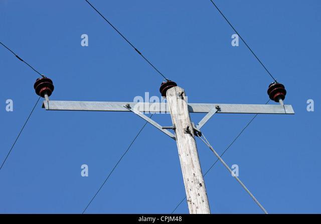 Telegrafenmast und Stromkabel gegen klar tiefblauen Himmel Stockbild