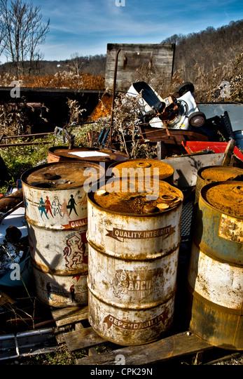 Haufen von industriellen Schmutz und Öl Fässer, einen ausrangierten Rasenmäher und anderen Müll Stockbild
