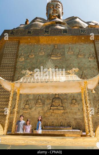 Junge Touristen unter große Statue von Buddha stehend Stockbild