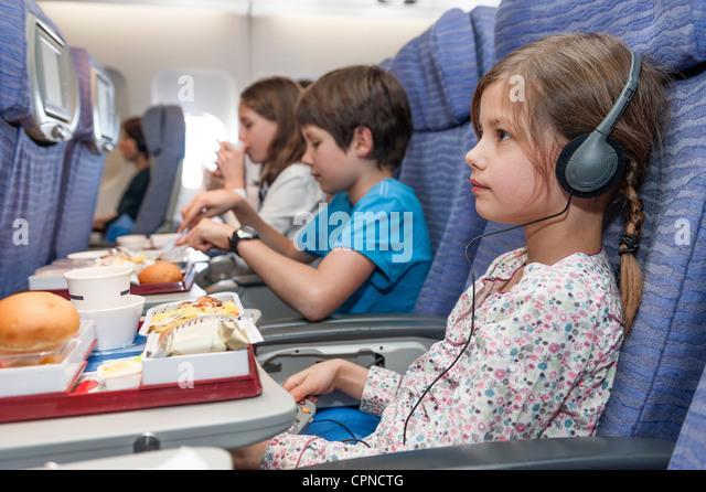 Mädchen Film auf Flugzeug, Fluggesellschaft Mahlzeit auf Tablett-Tisch - Stock-Bilder