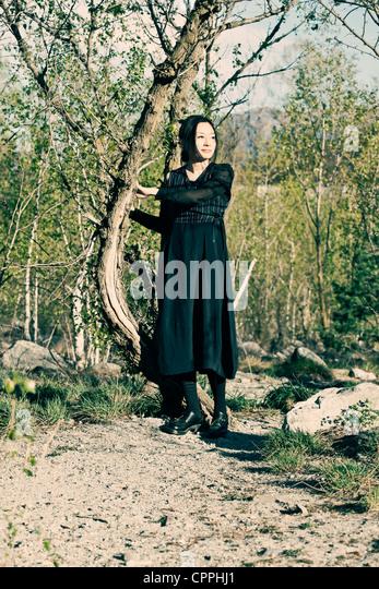 Eine junge Frau steht in der Sonne in einem Wald im Frühjahr Stockbild