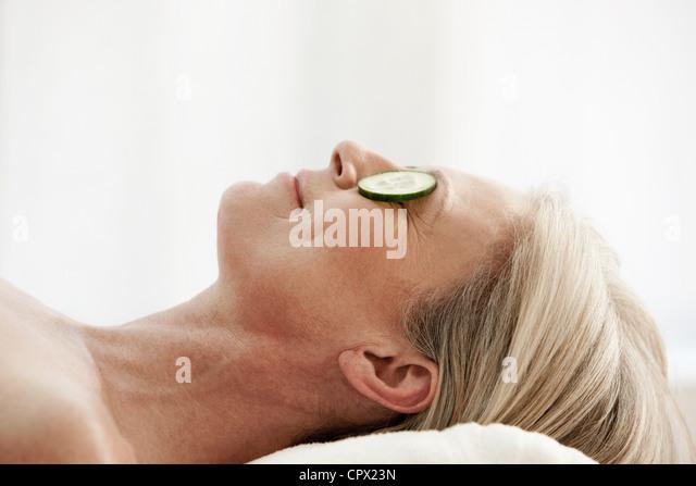 Reife Frau mit Gurkenscheiben über Augen entspannen Stockbild