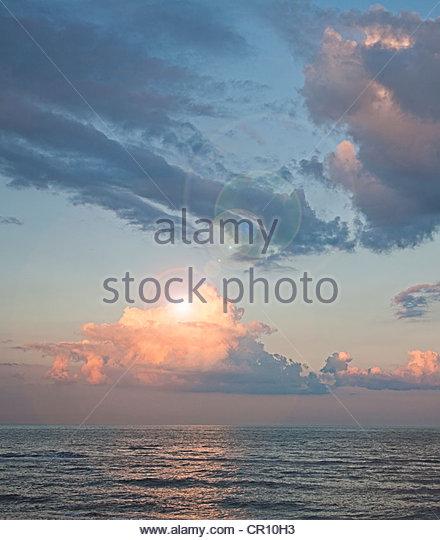 Wolken am blauen Himmel über Meer Stockbild