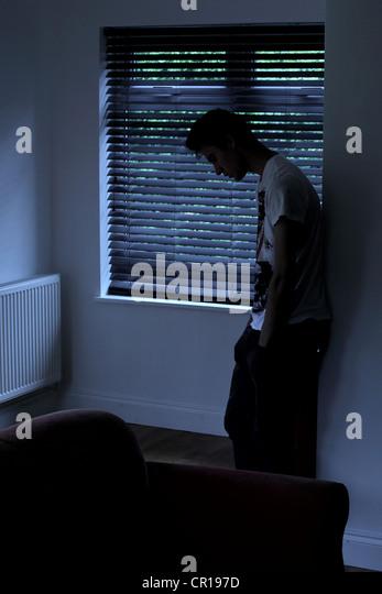 Junger Mann in einem dunklen Raum mit Blick durch ein Fenster Blind sitzen. Modell und Besitz (Fotograf) veröffentlicht. Stockbild