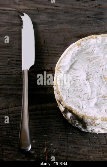 Camembert mit einem Käsemesser auf einer rustikalen Holzoberfläche Stockbild