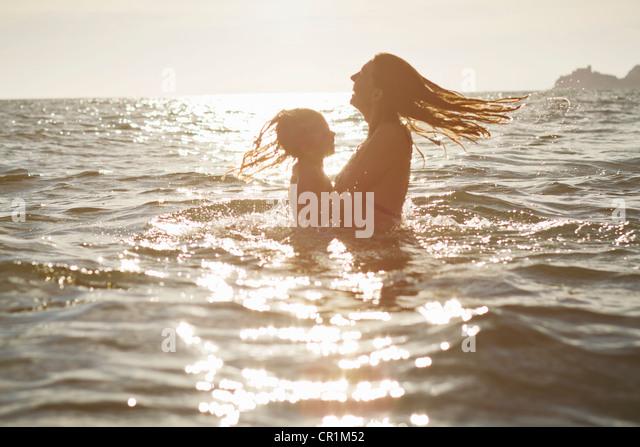 Mutter und Tochter spielen im Ozean Stockbild