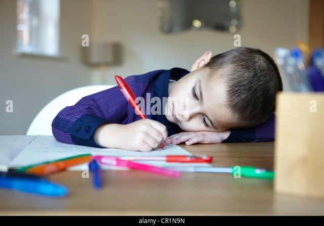 Schüler schreiben am Schreibtisch Stockbild