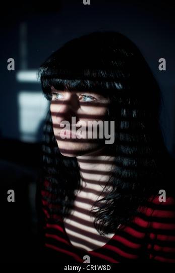 Frau im Schatten der Jalousien Stockbild