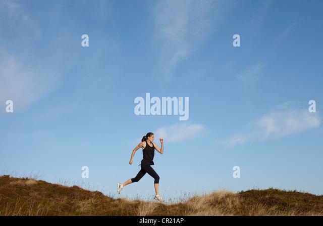 Frau läuft auf ländlichen Hügel Stockbild