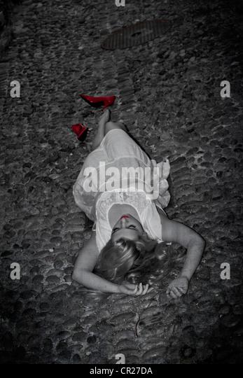 junge Frau liegt auf der Straße auf einer Kopfsteinpflaster in einem weißen Kleid mit roten pumps Stockbild