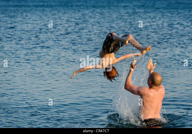 Vater und Sohn im Meer planschen Stockbild