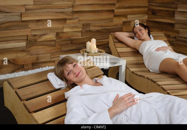 Glückliche junge Frau am Holzstuhl im Wellnesscenter entspannen Stockbild