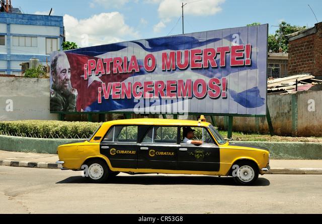 Gestreckte Lada-Taxi vor eine Werbetafel mit politischer Propaganda darauf, Fidel Castro, Socialismo o muerte Stockbild