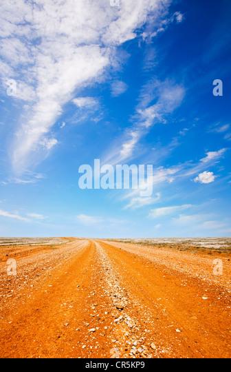 Rote Piste im australischen Outback, unter einem flammenden heißen blauen Himmel. Stockbild