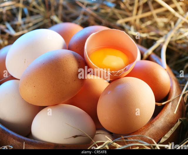 Hühnereier im Stroh. Ein Ei ist gebrochen. Stockbild