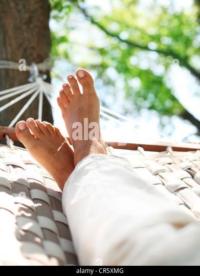 Füße in einer Hängematte auf einem Sommer-Natur-Hintergrund. Stockbild