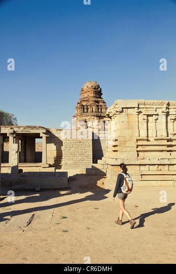 Indien, Karnataka, Hampi, junge Frau, die zu Fuß in Richtung Tempel Stockbild