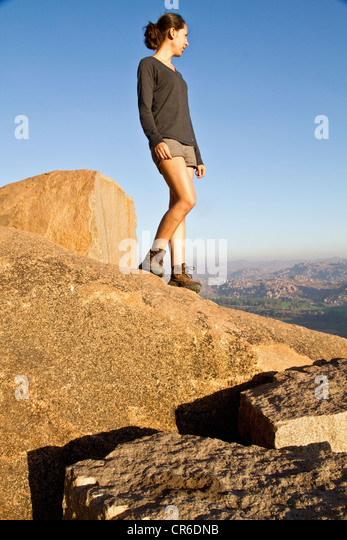Indien, Karnataka, Hampi, junge Frau, die auf Felsen Stockbild