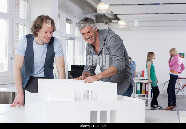 Deutschland, Bayern, München, Männer zusehen Architekturmodell in Büro, Kollegen reden im Hintergrund Stockbild