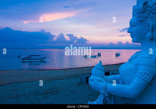 Indonesien, Bali, Sanur, Statue mit Meer im Hintergrund in der Abenddämmerung Stockbild