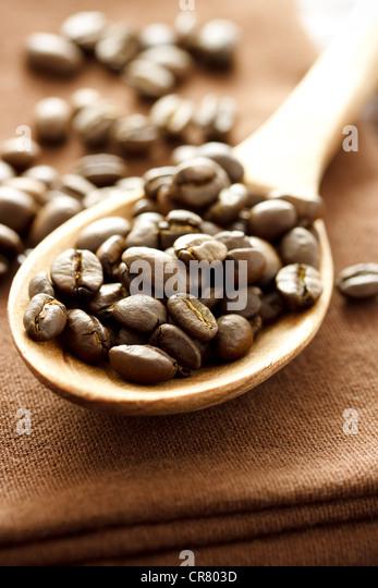 Kaffeebohnen in Holzlöffel auf braunem Tuch Stockbild