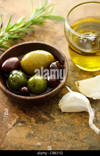 Olivenöl und gemischte Oliven mit Knoblauch Stockbild