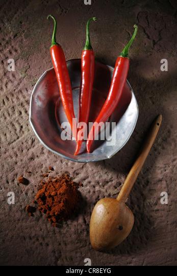 Drei Chili Paprika (Capsicum) auf einem Zinn-Teller mit einem Holzlöffel und Chili-Pulver auf einem rustikalen Stockbild