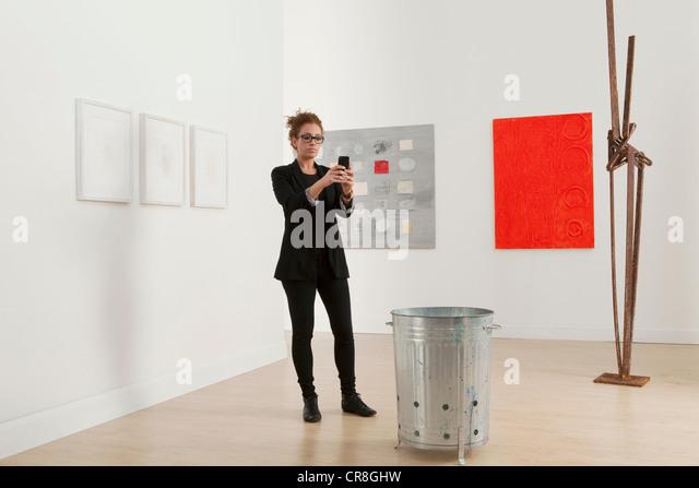 Junge Frau mit Handy Galerie Kunstwerk fotografieren Stockbild