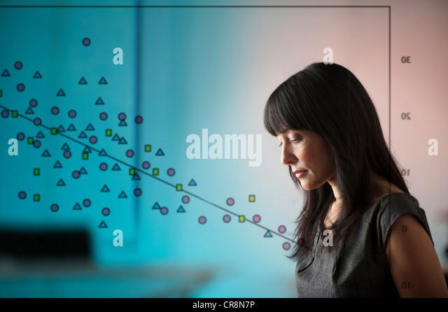 Reife Frau mit Diagramm von Shapes-Fenster Stockbild