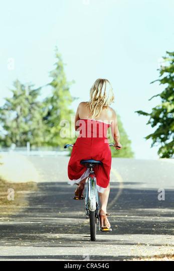 Frau Reiten Fahrrad auf Landstraße Stockbild