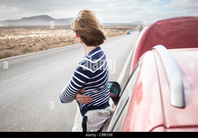 Frau mit aufgeschlüsselt Auto auf Landstraße Stockbild