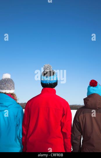 Menschen tragen Hüte und Mäntel im Schnee Stockbild