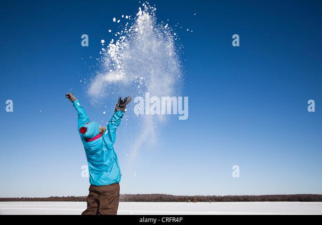 Frau spielt mit Schnee im freien Stockbild