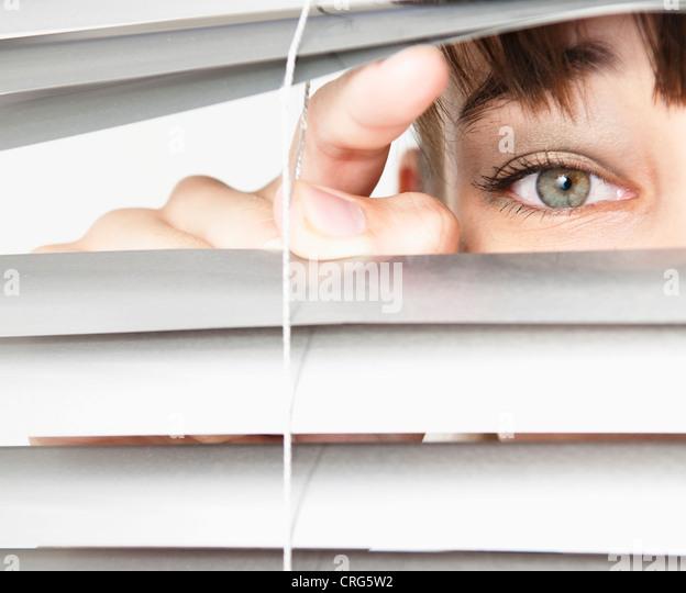 Frau spähen durch Jalousien Stockbild
